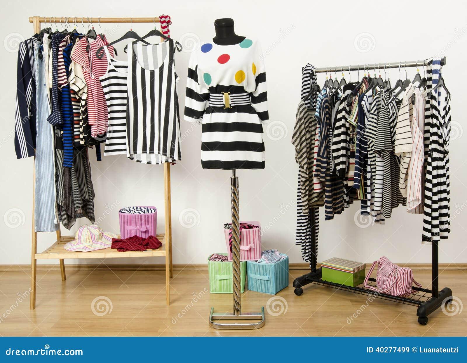 Одевать шкаф с striped одеждами аранжировал на вешалках.