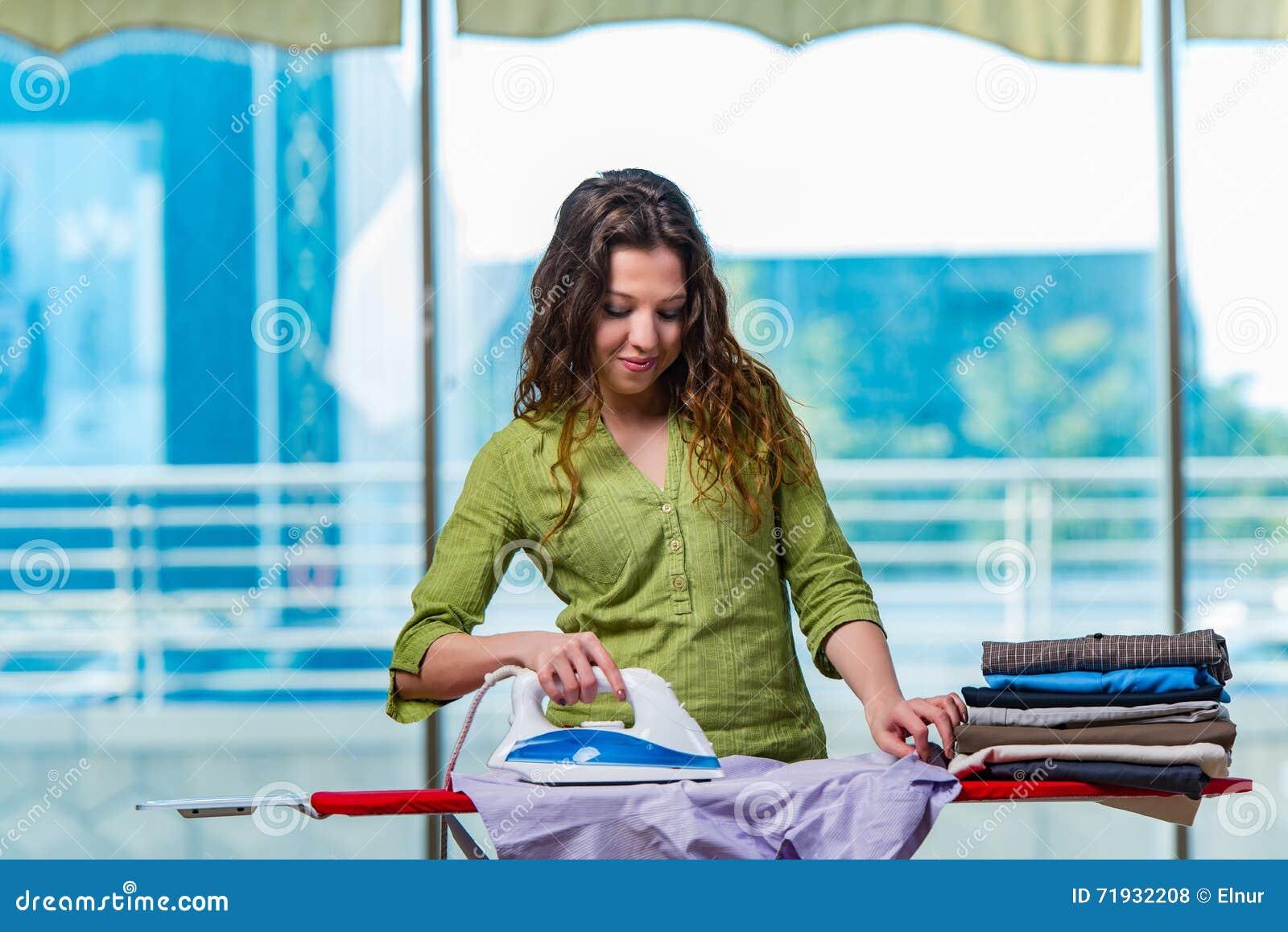 Одежда молодой женщины утюжа на борту