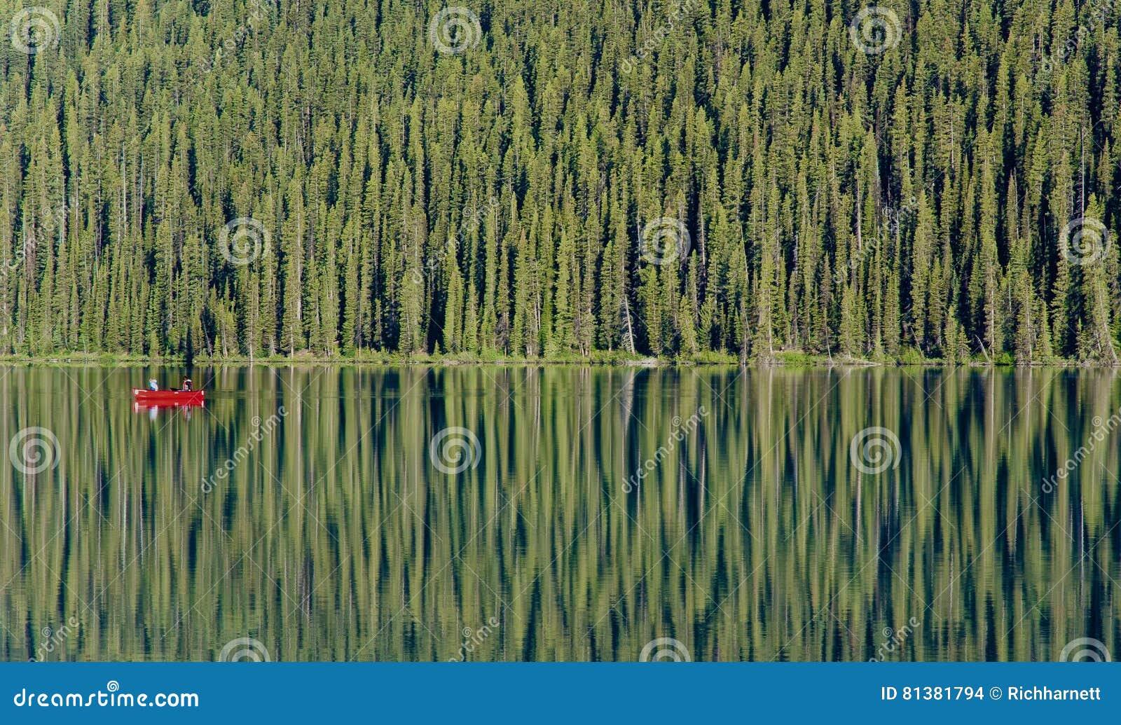 Одиночное красное каное плавает на стекловидное Lake Louise