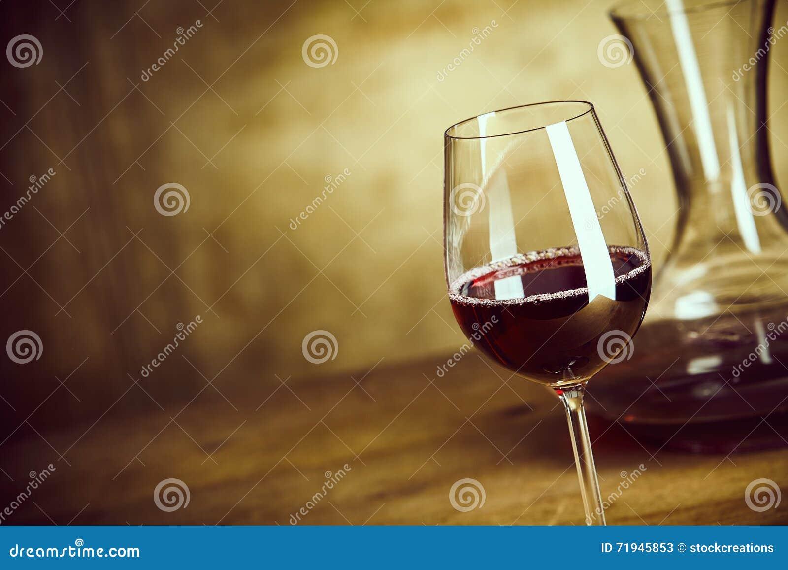 Одиночное стекло красного вина наряду с графинчиком