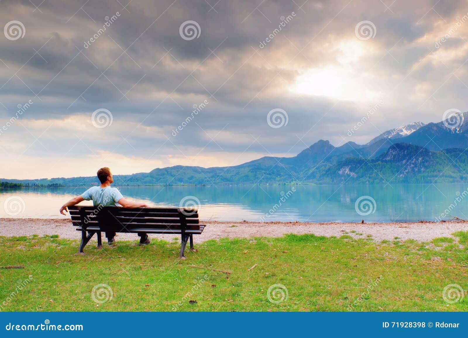 Один человек сидит на стенде около лазурного озера горы человек ослабляет