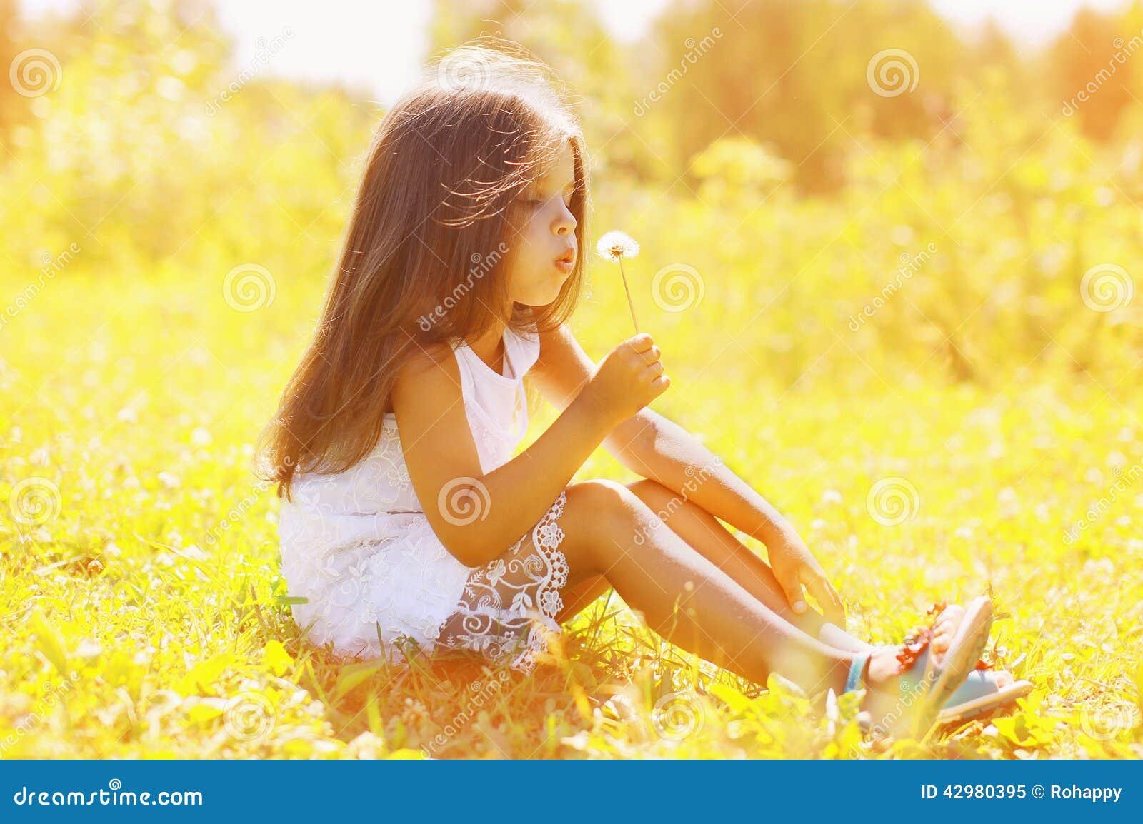 Одуванчик маленького ребенка дуя в солнечном летнем дне