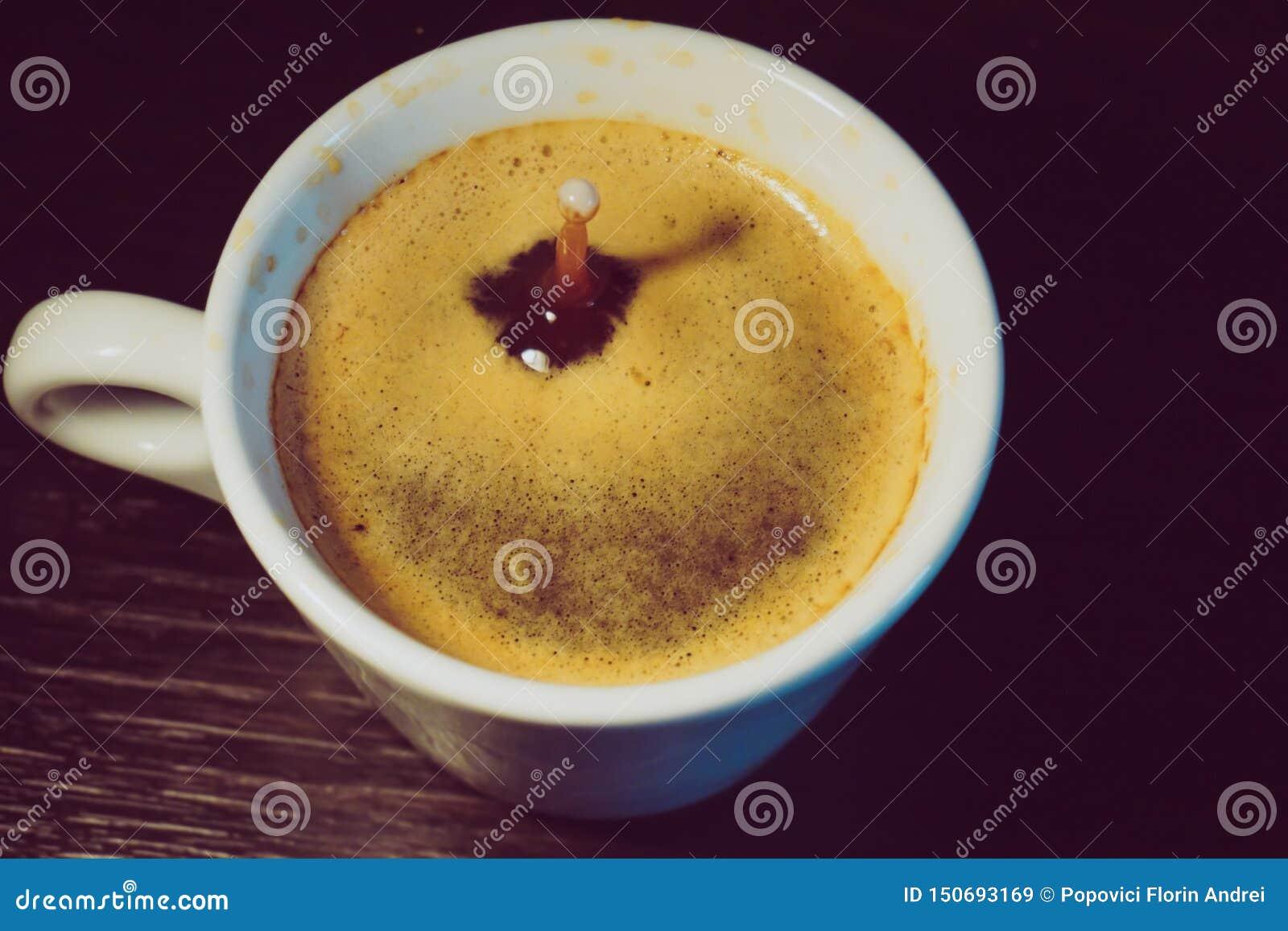 Падение молока понижаясь в чашку кофе