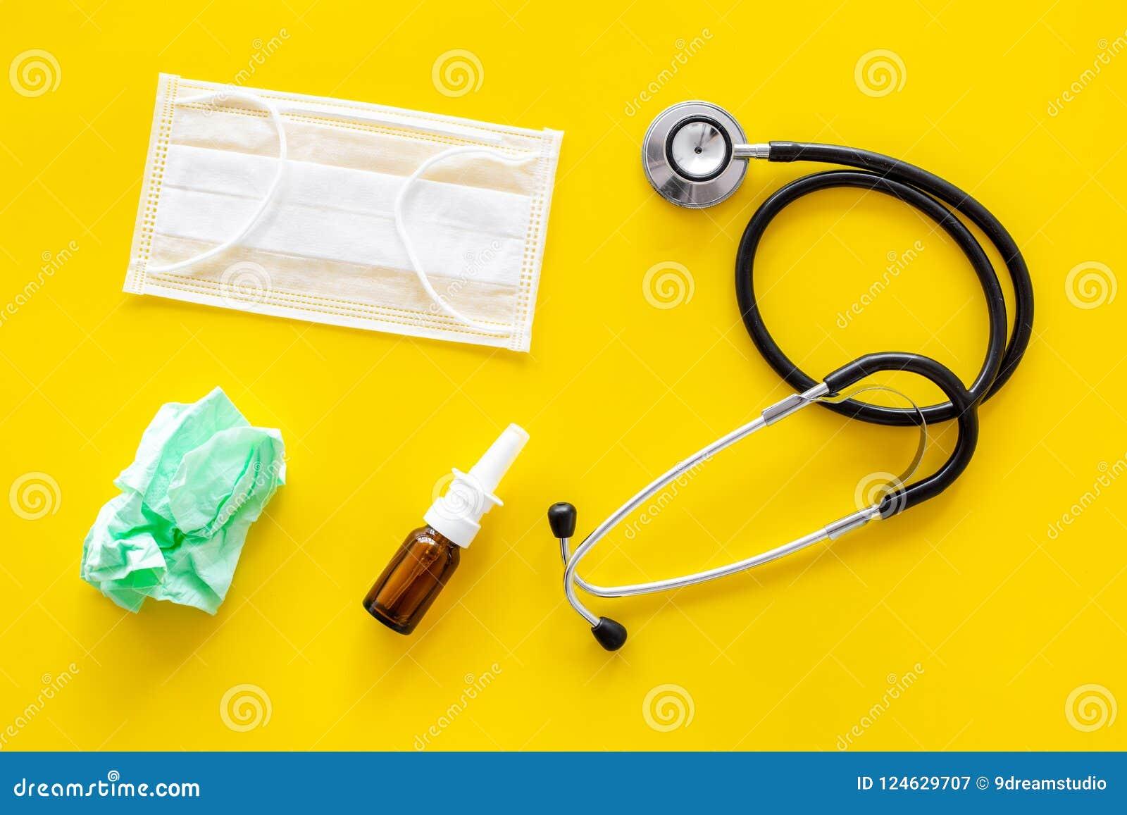 Падения гриппа Идущая концепция носа Сморщенная салфетка около стетоскопа и лицевой щиток гермошлема на желтом взгляд сверху пред