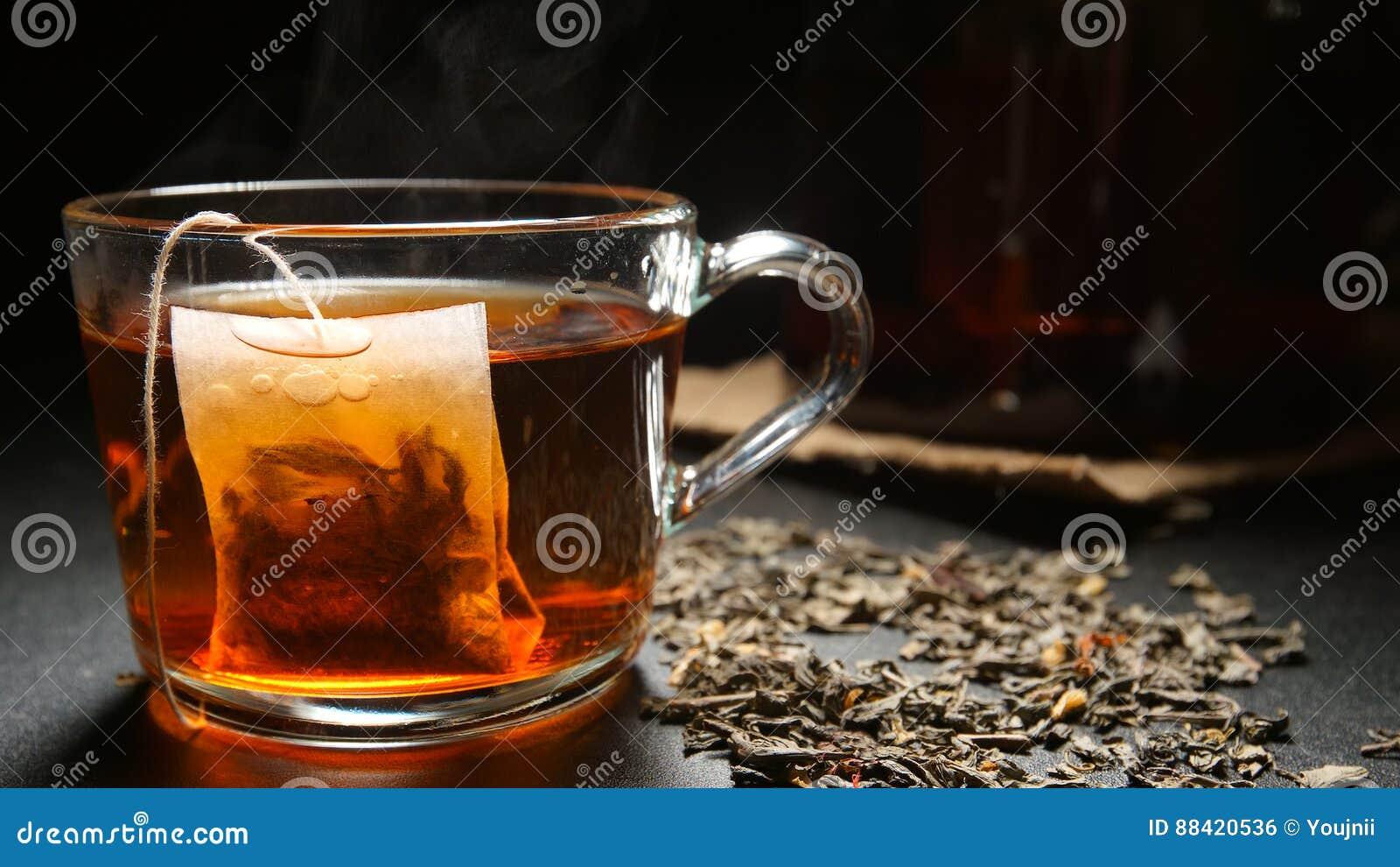 Пакетик чая в горячей чашке чая на таблице