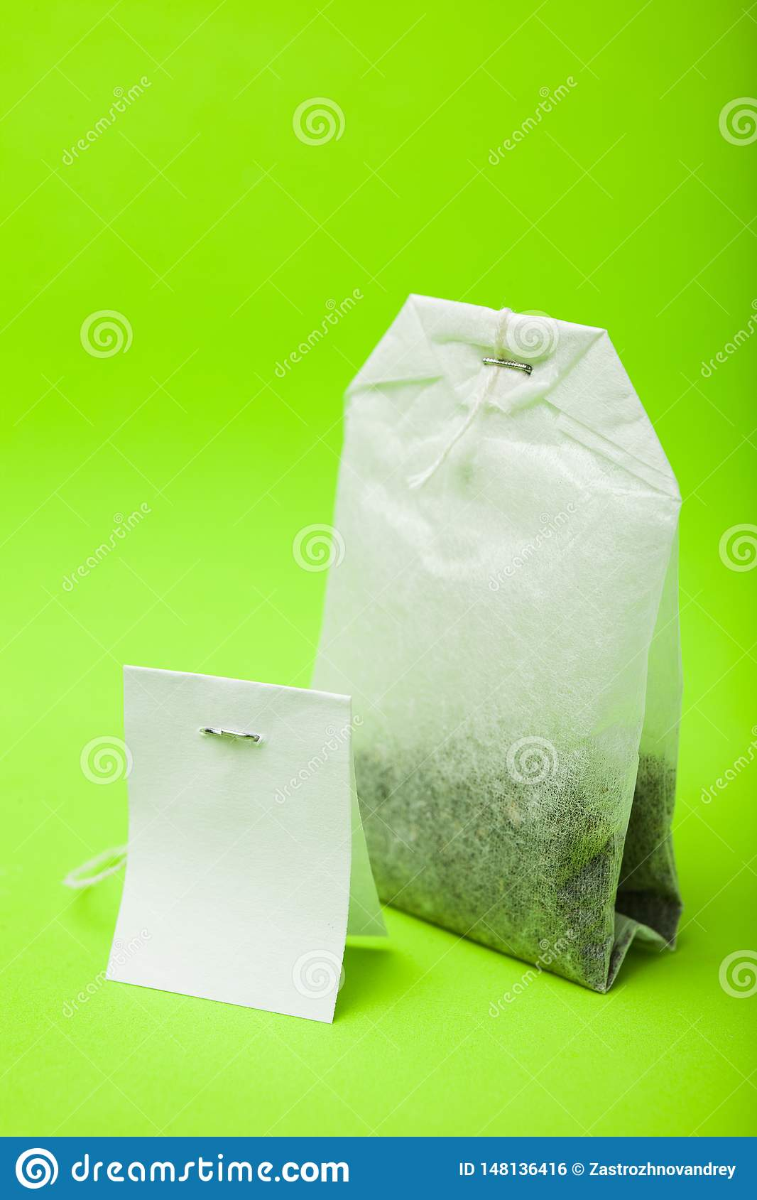 Пакетик чая с пустым ярлыком Изолированный на зеленой предпосылке r