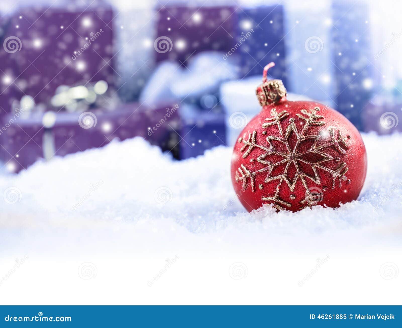 Пакеты подарка рождества шарика свечи рождества на заднем плане - идущ снег