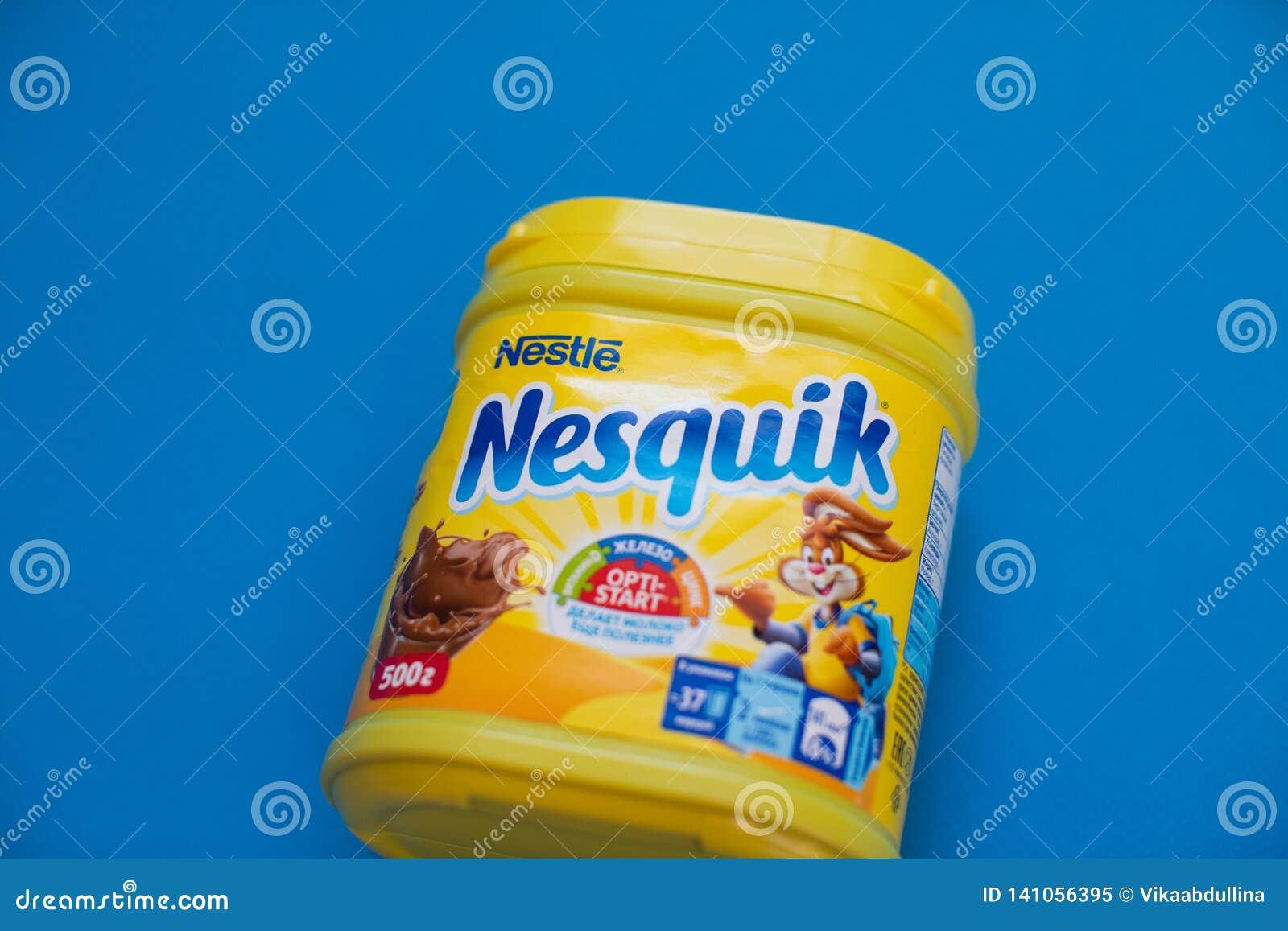 Пакет напитка Nesquik шоколада и какао Nestle на голубой предпосылке