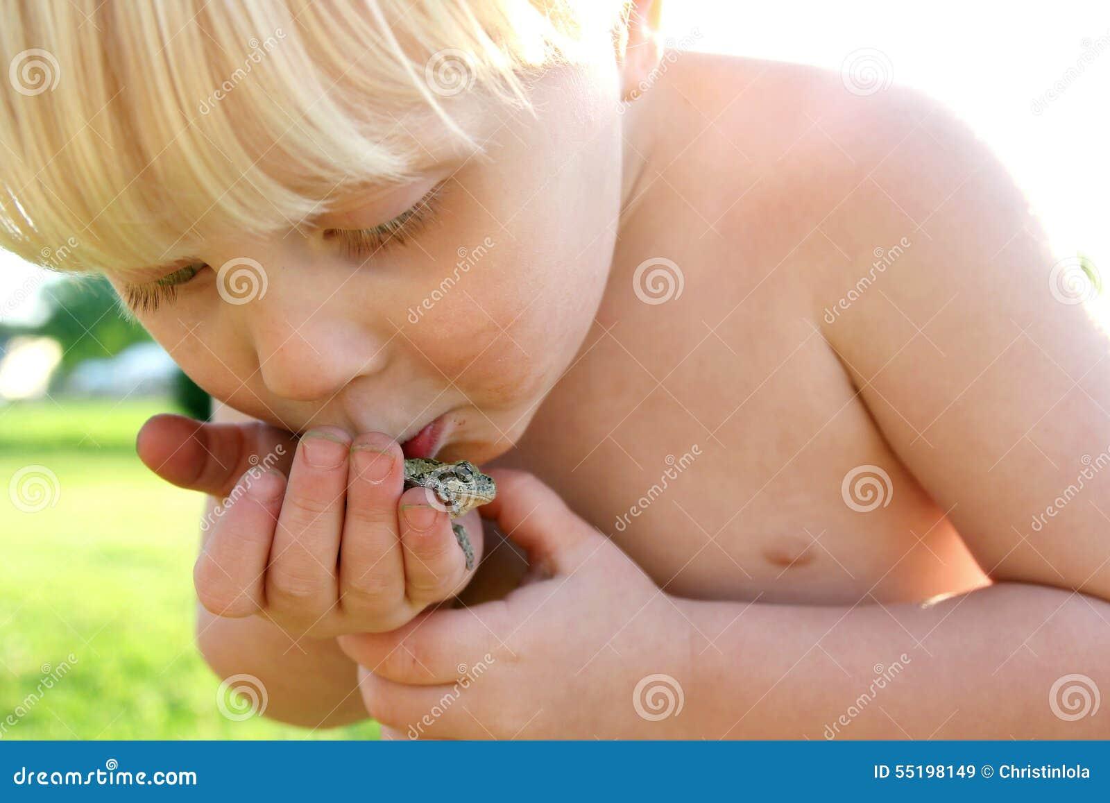 Пакостный малыш играя внешнюю целуя лягушку