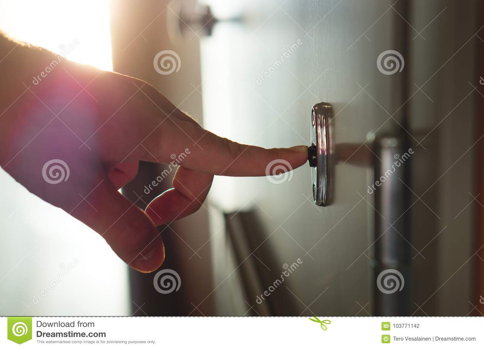 Палец отжимая дверной звонок в солнечном жилом доме