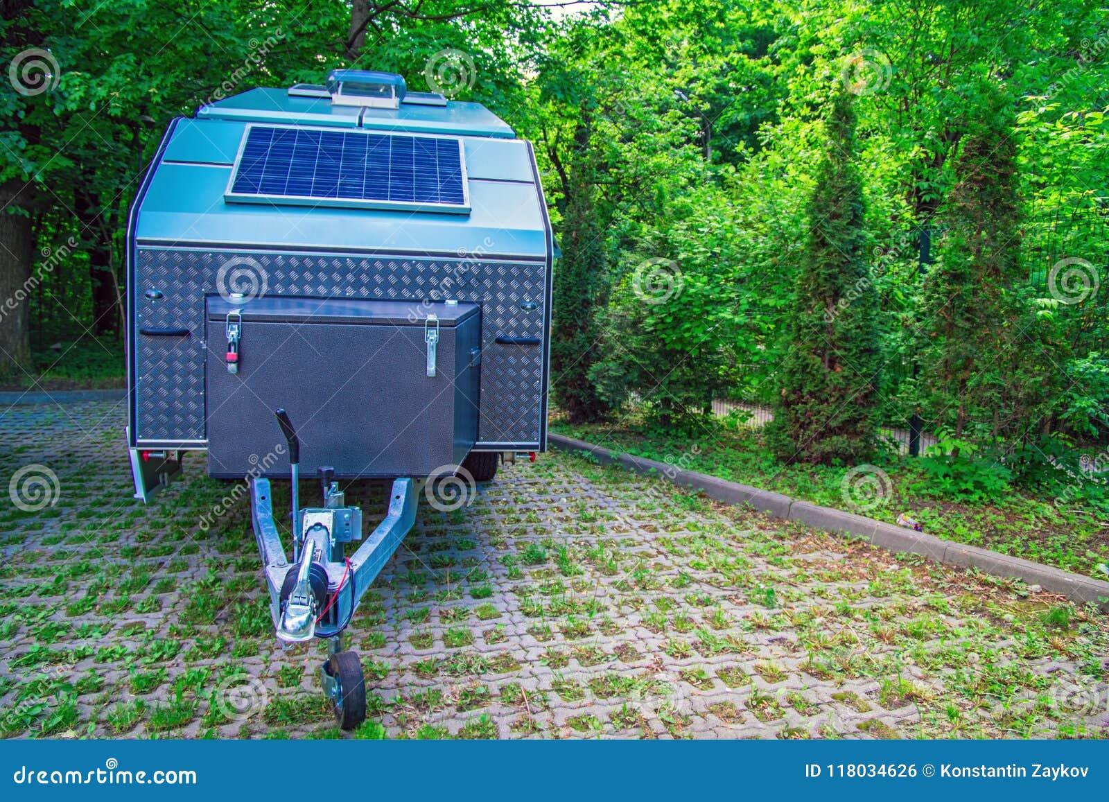 Панель солнечных батарей фиксирована на туристском трейлере Внедорожный трейлер стоит в месте для стоянки на предпосылке толстой
