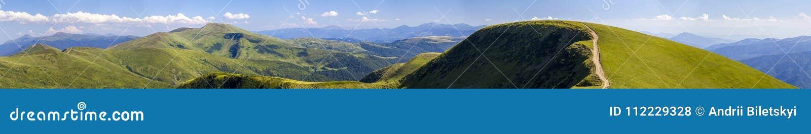 Панорама зеленых холмов в горах лета с дорогой гравия для