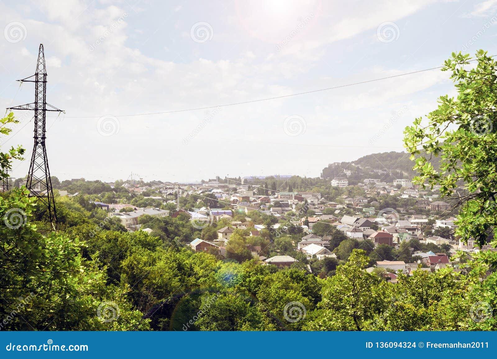 Панорама маленького города и высоковольтной электрической башни для того чтобы поставить электричество к населению