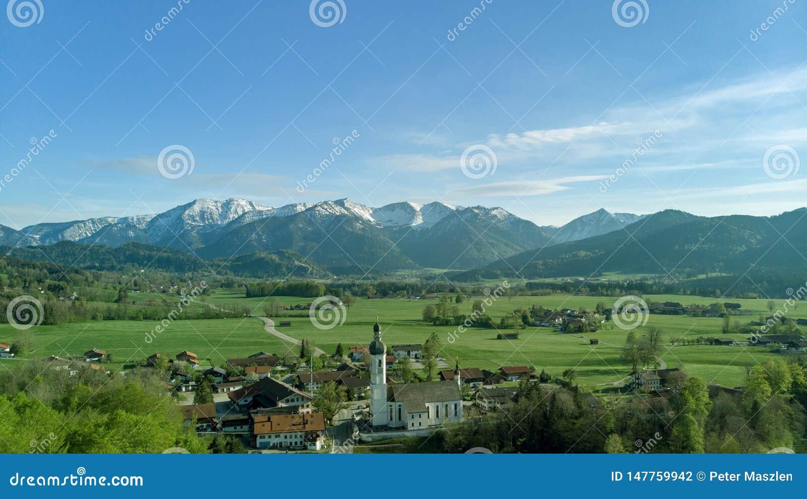 Панорамный вид баварской деревни в красивом ландшафте близко к горным вершинам