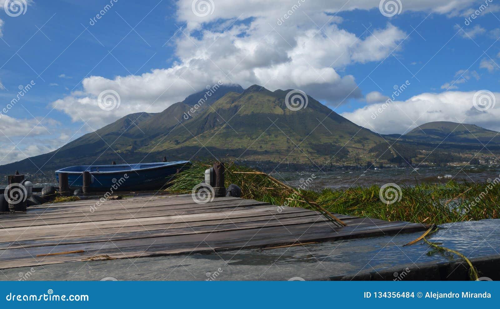 Панорамный вид вулкана Imbabura увиденного от лагуны Сан Pablo во дне с ясным голубым небом