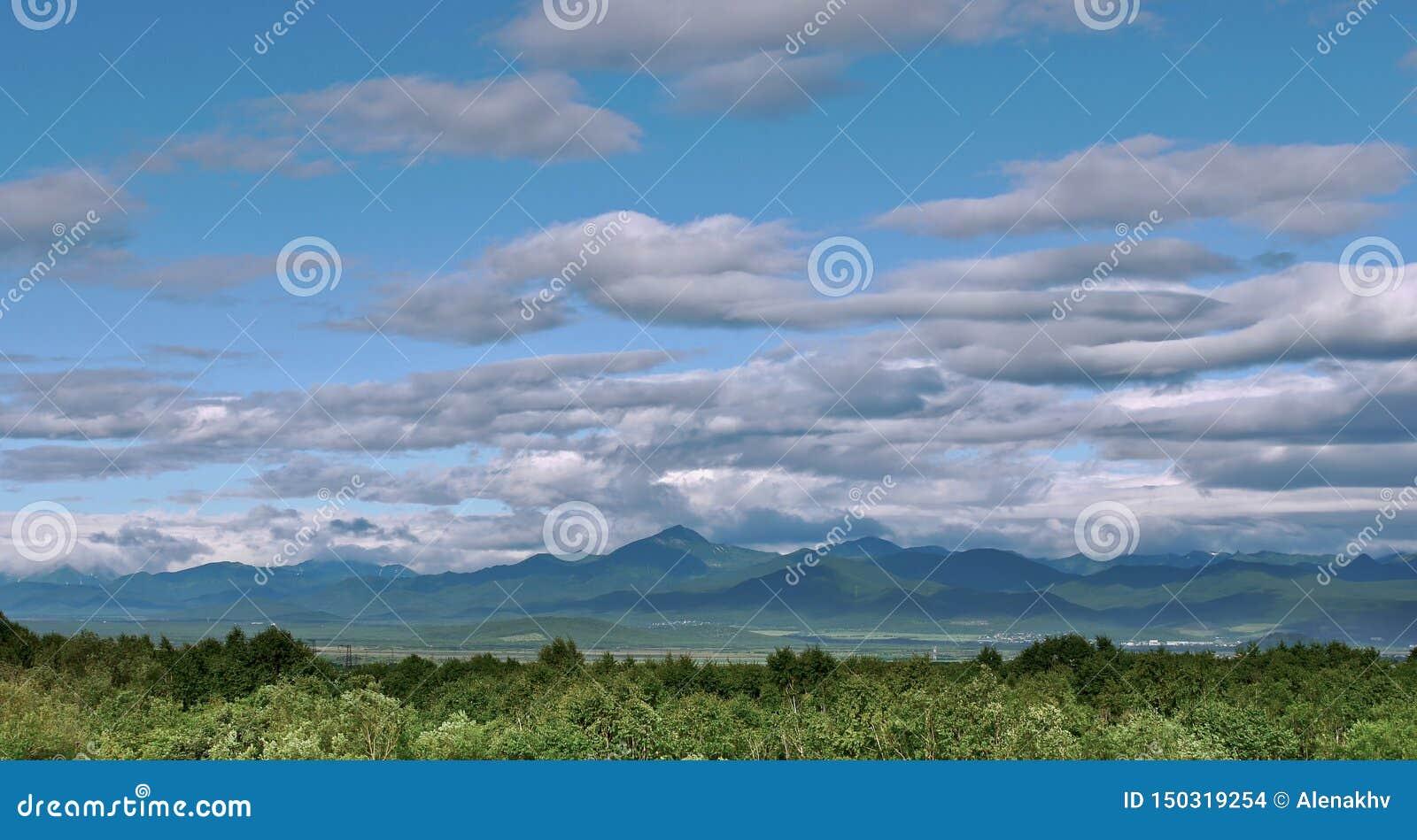 Панорамный вид красивых облаков над долиной зеленого холма
