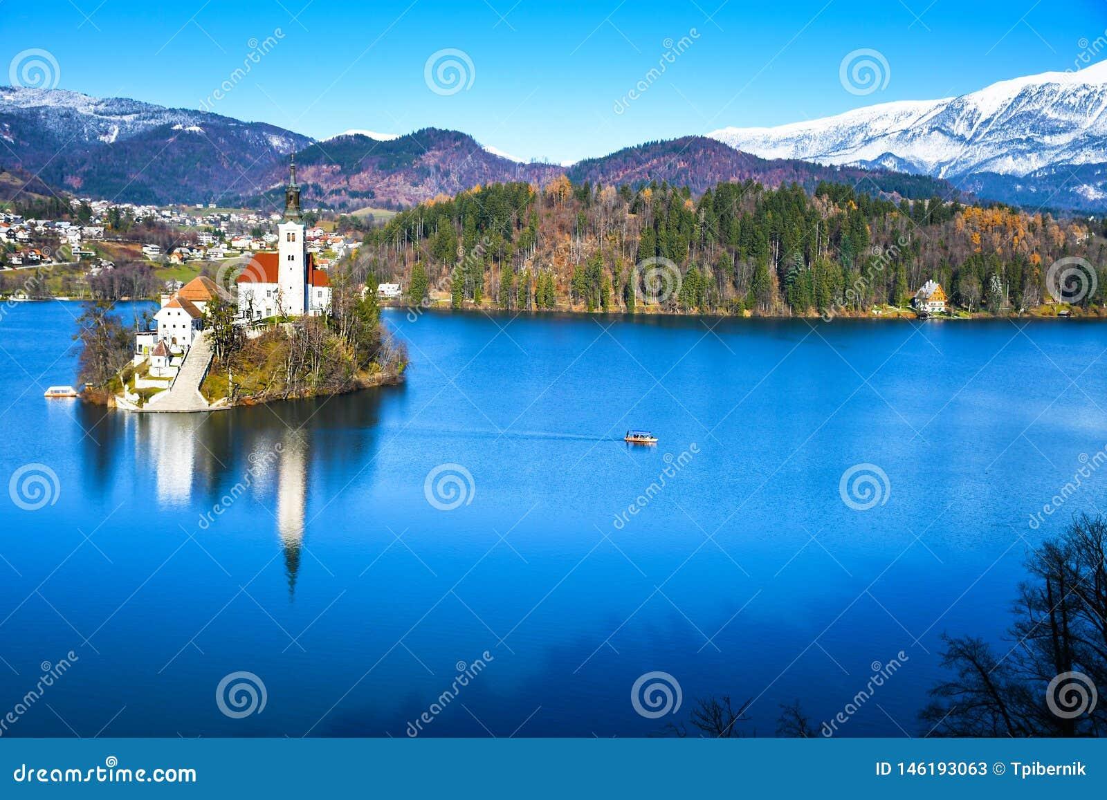 Панорамный вид небольшого естественного острова в середине высокогорного озера с церковью предназначенной к предположению Mary и