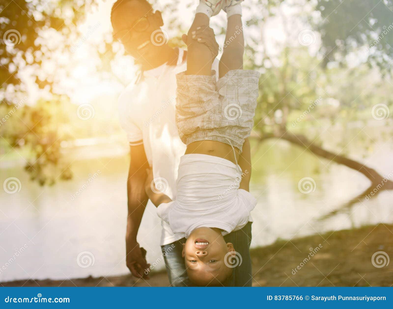 Папа держа сына вверх ногами в парке под солнечным светом