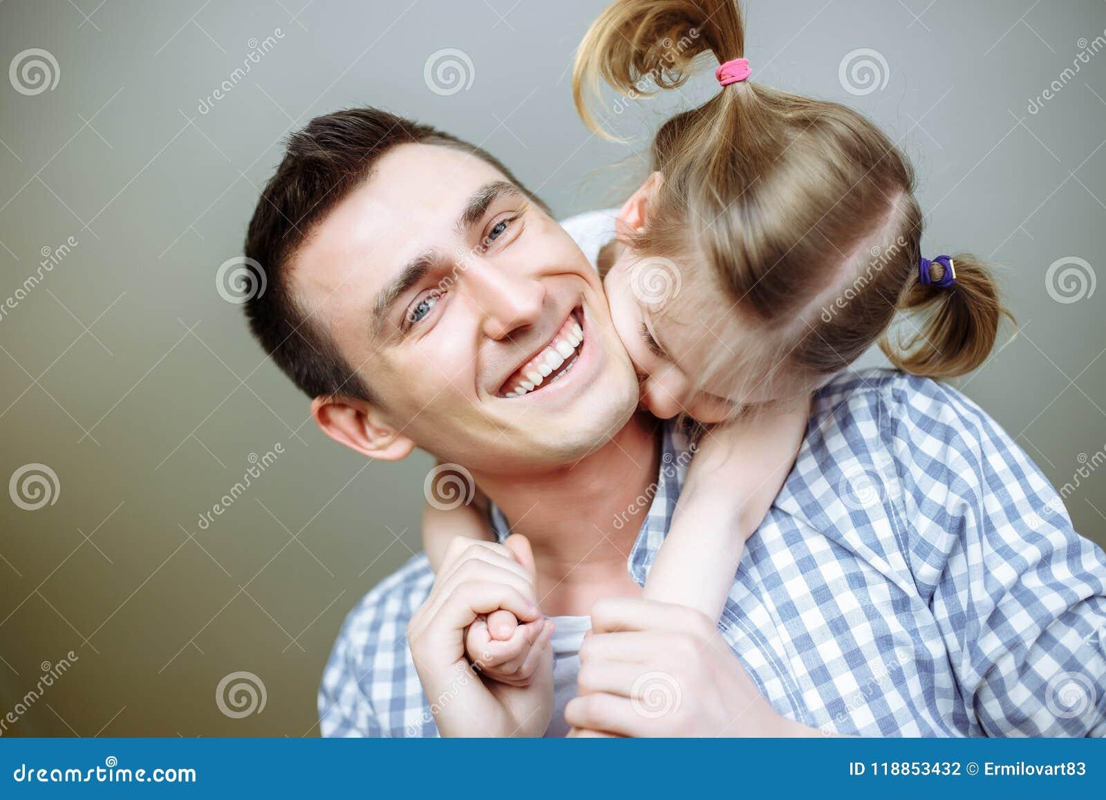 Папа и его девушка ребенка дочери играют, усмехаются и обнимаются Праздник и единение семьи поле глубины отмелое