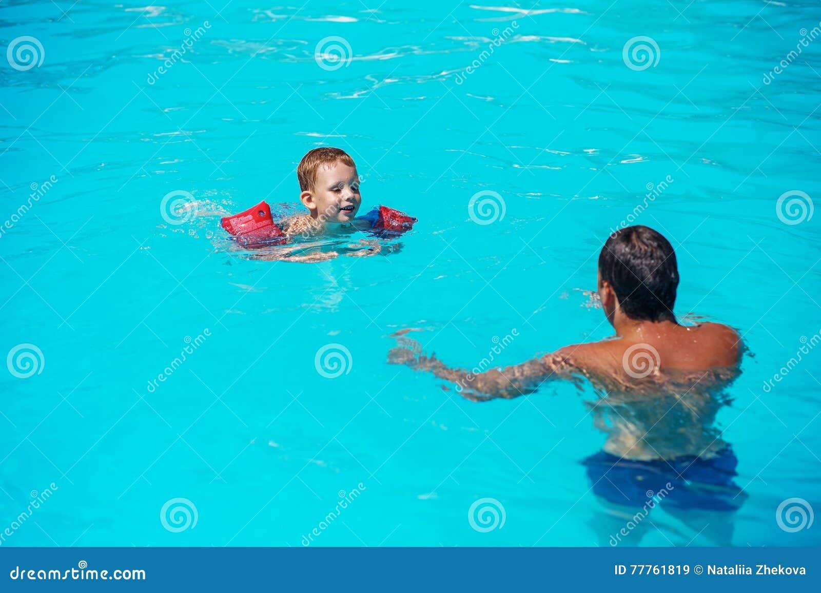 Папа и сын имея потеху в swimmming бассейне