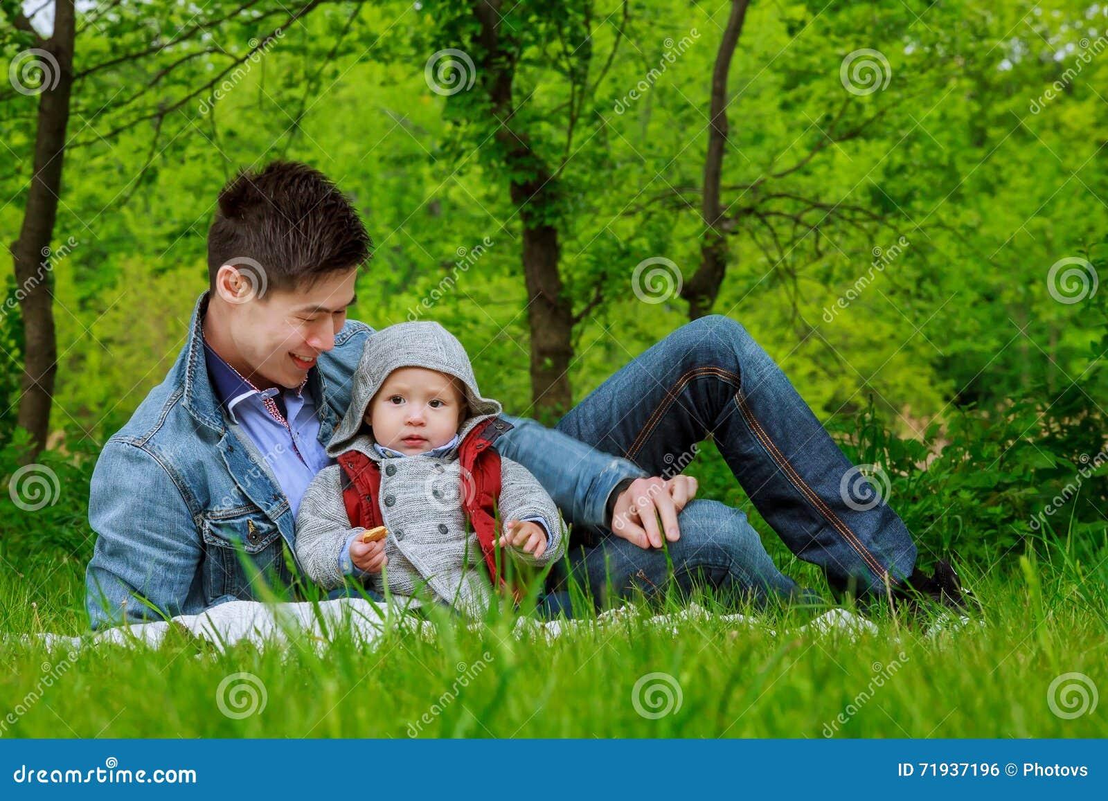 Папа при его сын играя в парке