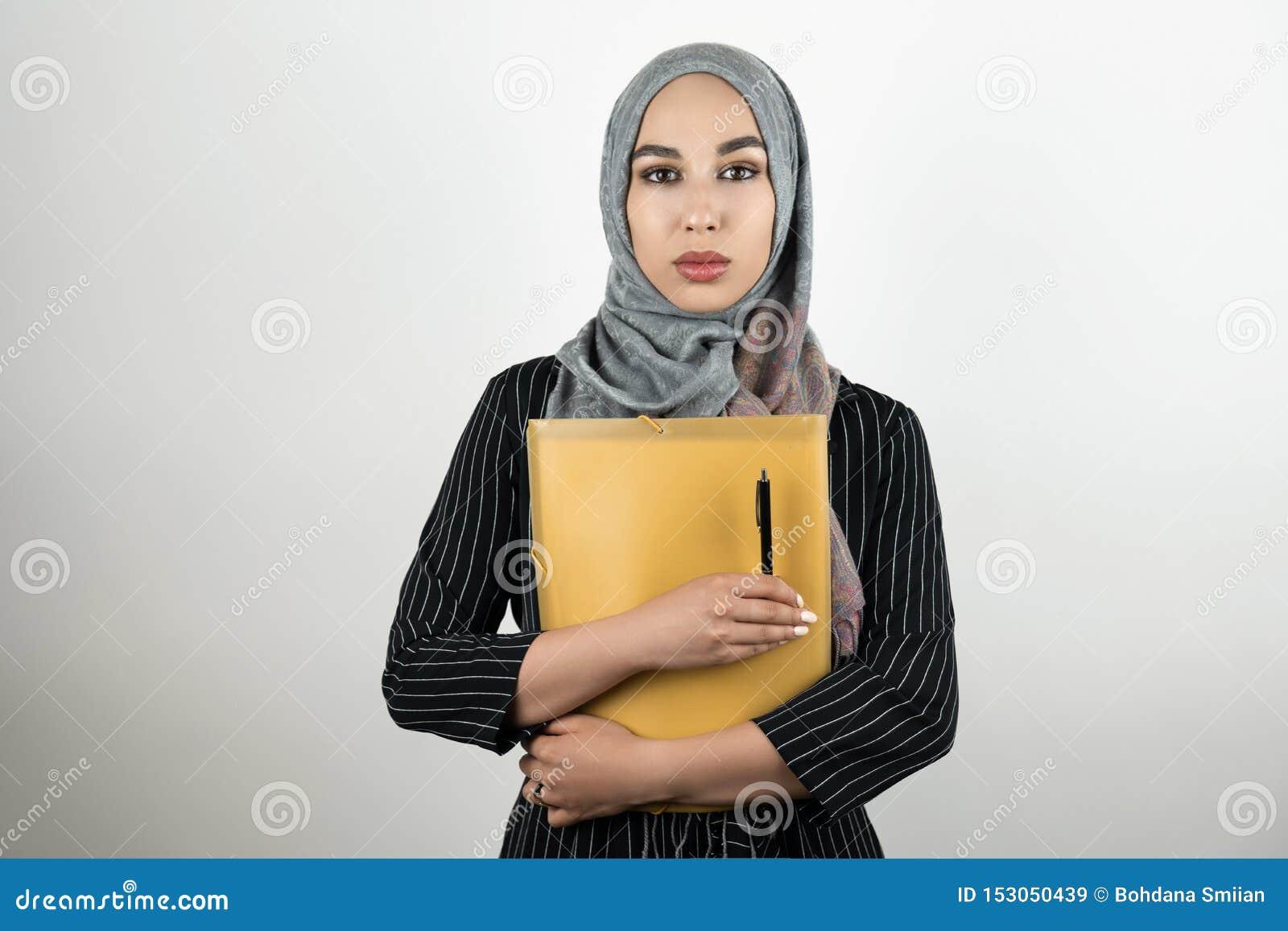Папка удерживания головного платка hijab тюрбана молодой красивой мусульманской бизнес-леди нося с документами и изолированная ру