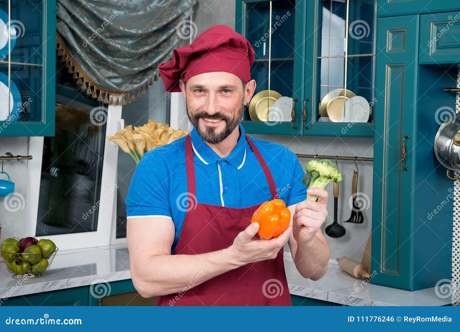 Паприка и брокколи в руках человека Усмехнутый шеф-повар с овощами в его руках Портрет бородатого парня на кухне