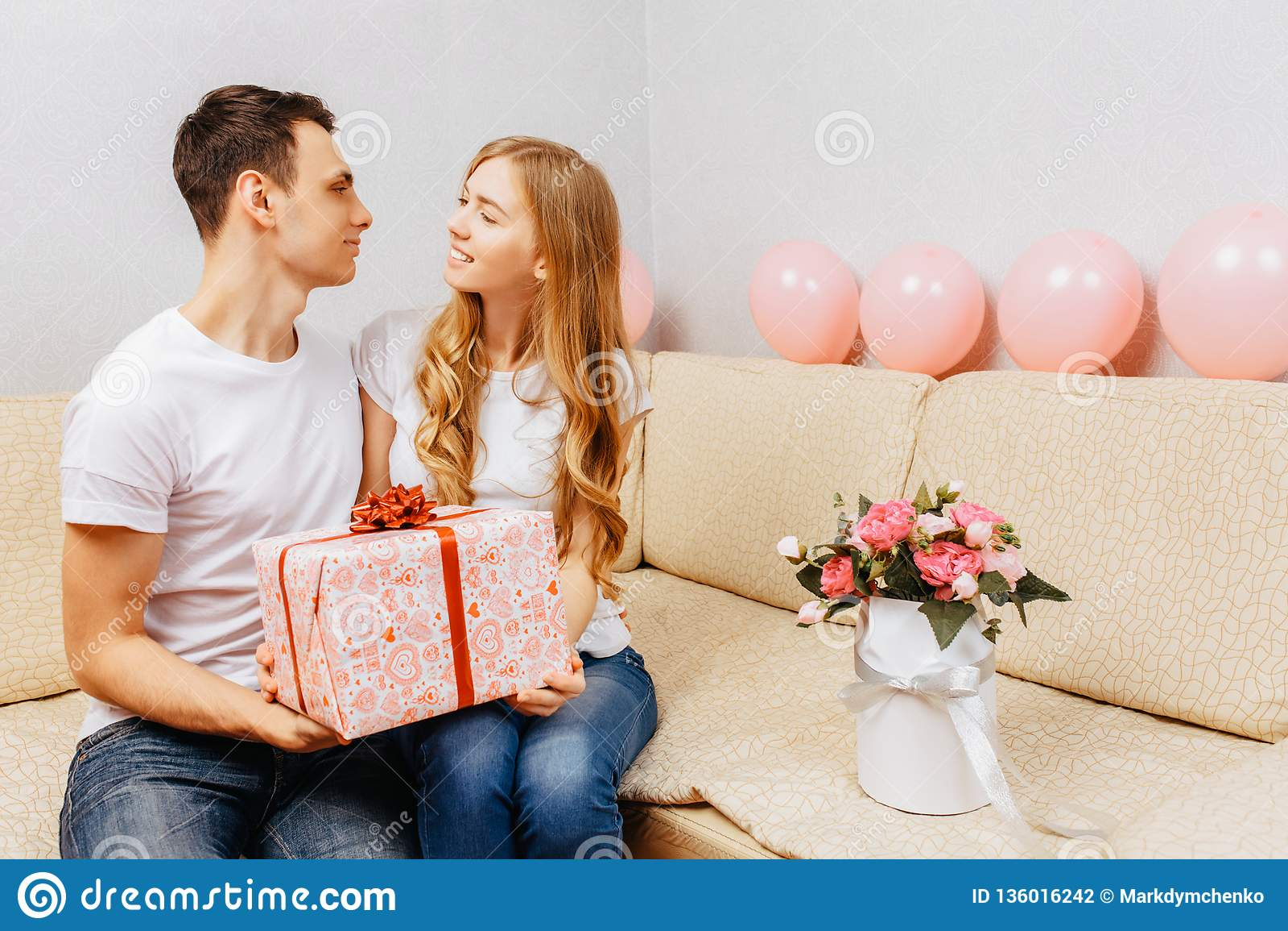 Пара в любов, человек дает подарок, женщину сидит дома на софе, концепции дня женщин