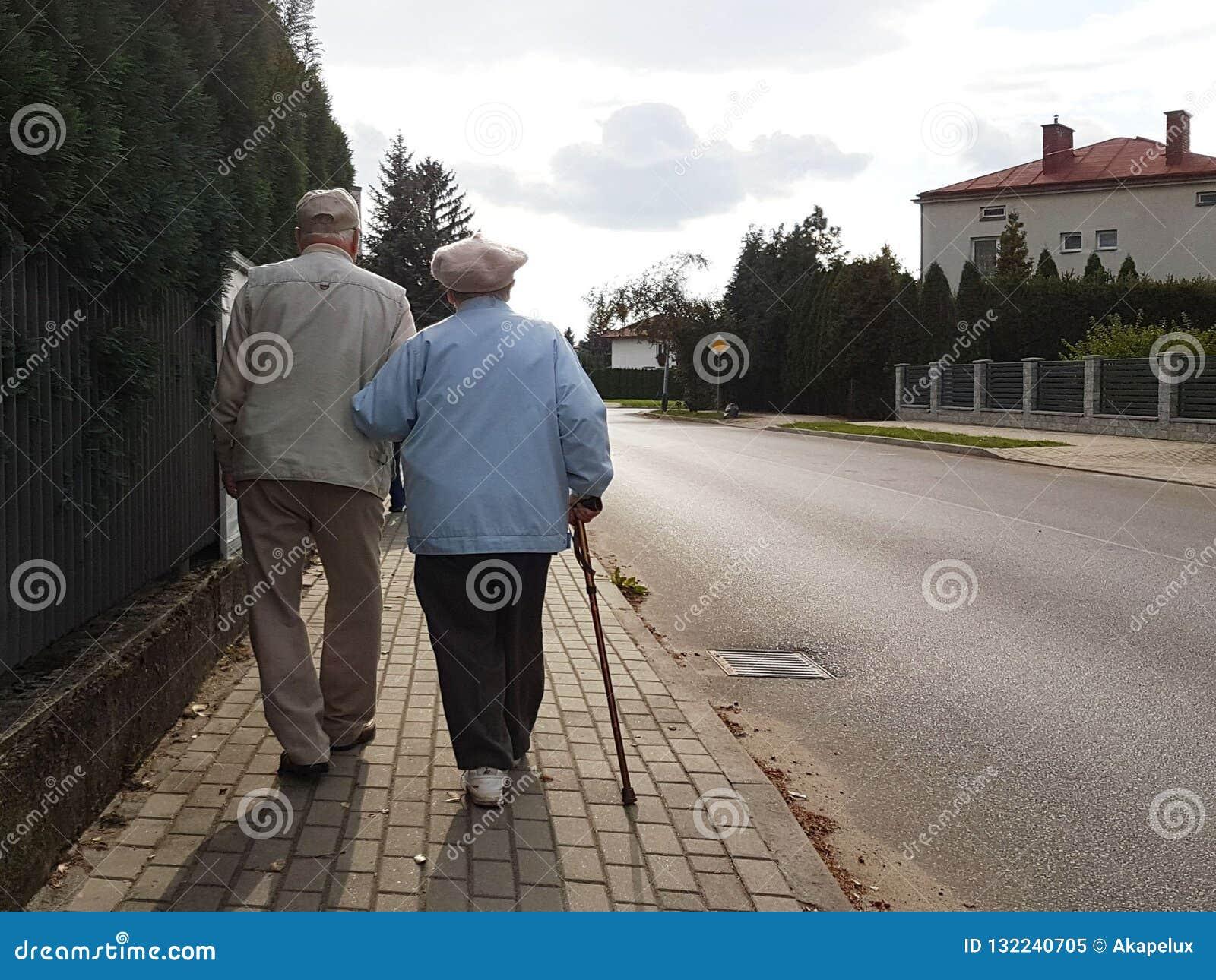 Пара престарелой прогулки вдоль тротуара вдоль дороги держа руки Дед и бабушка на прогулке в a
