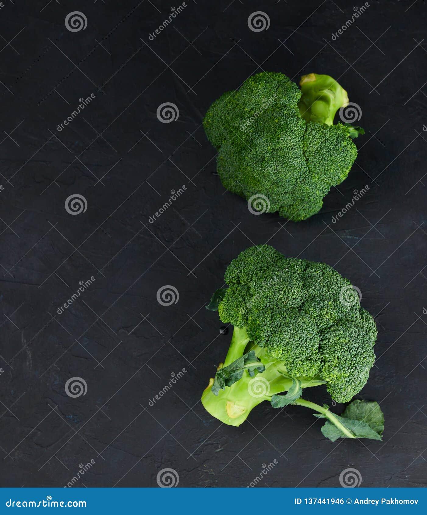 Пара свежего, сырцовая, брокколи на черной предпосылке взгляд сверху еда здоровая