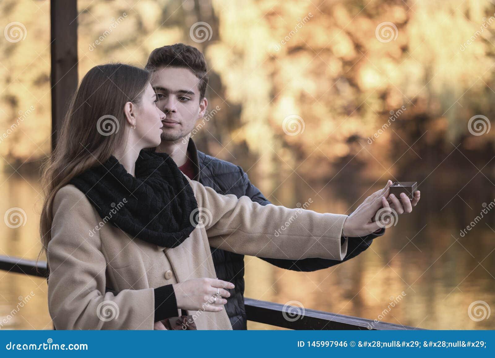 Парень делает предложение к девушке Молодая любящая пара стоит в парке осени с желтыми деревьями Человек