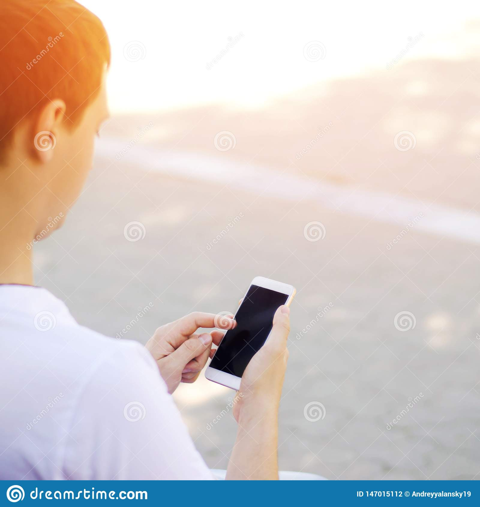 Парень держит мобильный смартфон и смотрит экран зависимость телефона, социальные сети работа в Интернете
