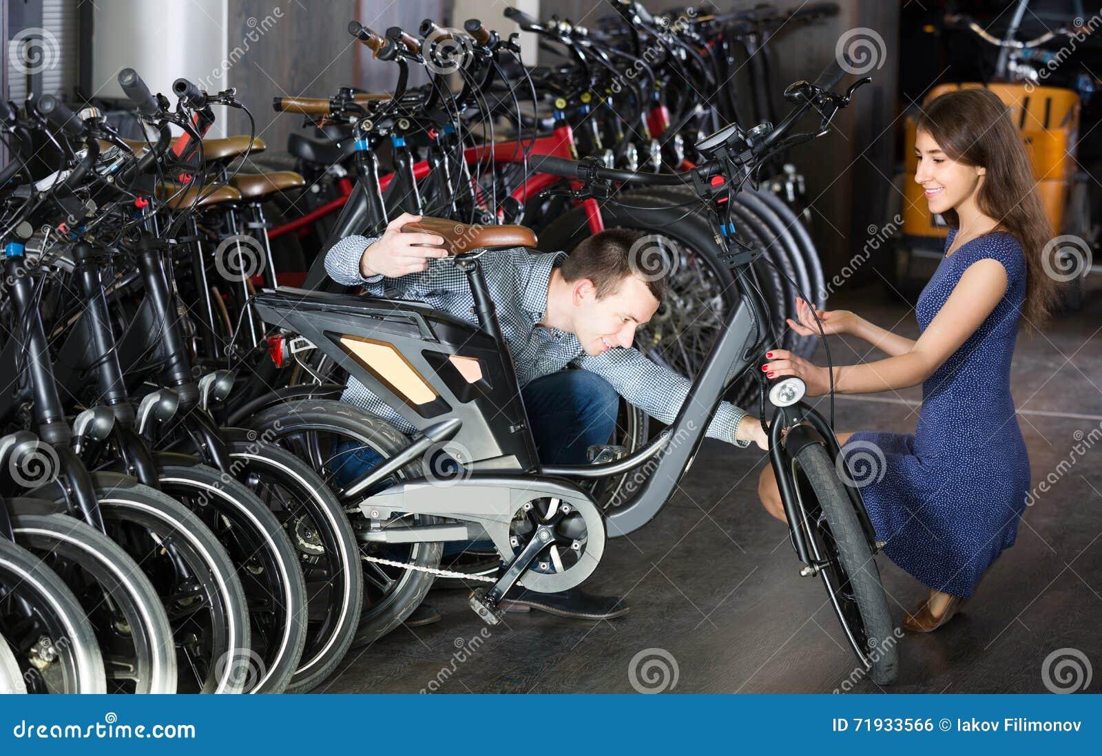 Парень порции работника взрослый для того чтобы выбрать велосипед на арендном агенстве