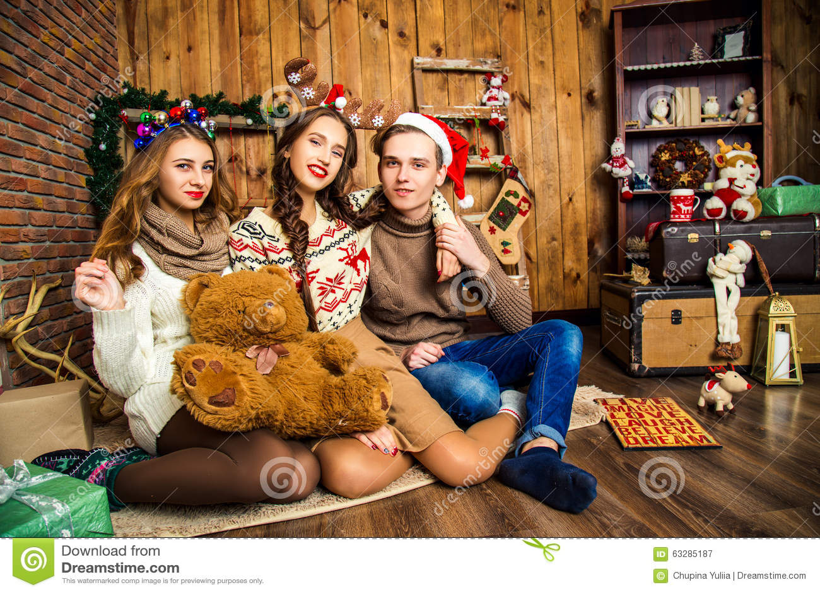 Парень с 2 девушками в комнате с украшениями рождества