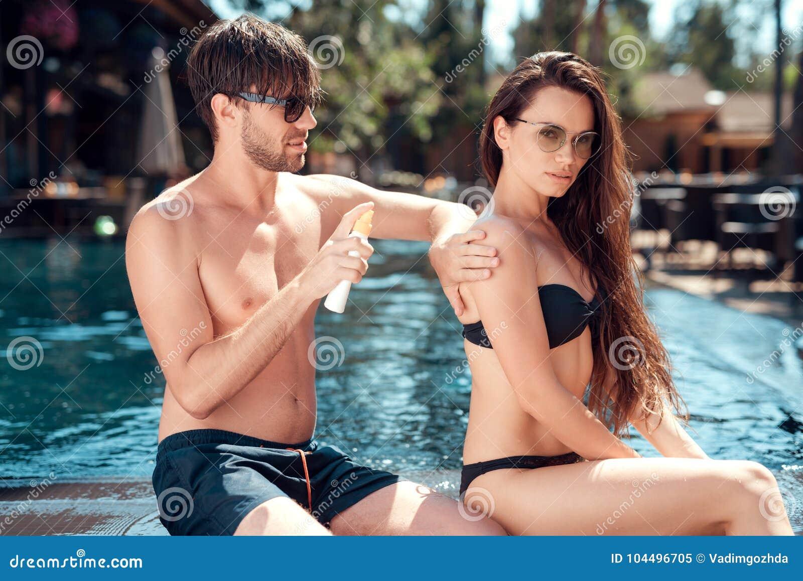 Парень трет заднюю часть ` s девушки с солнцезащитным кремом около бассейна