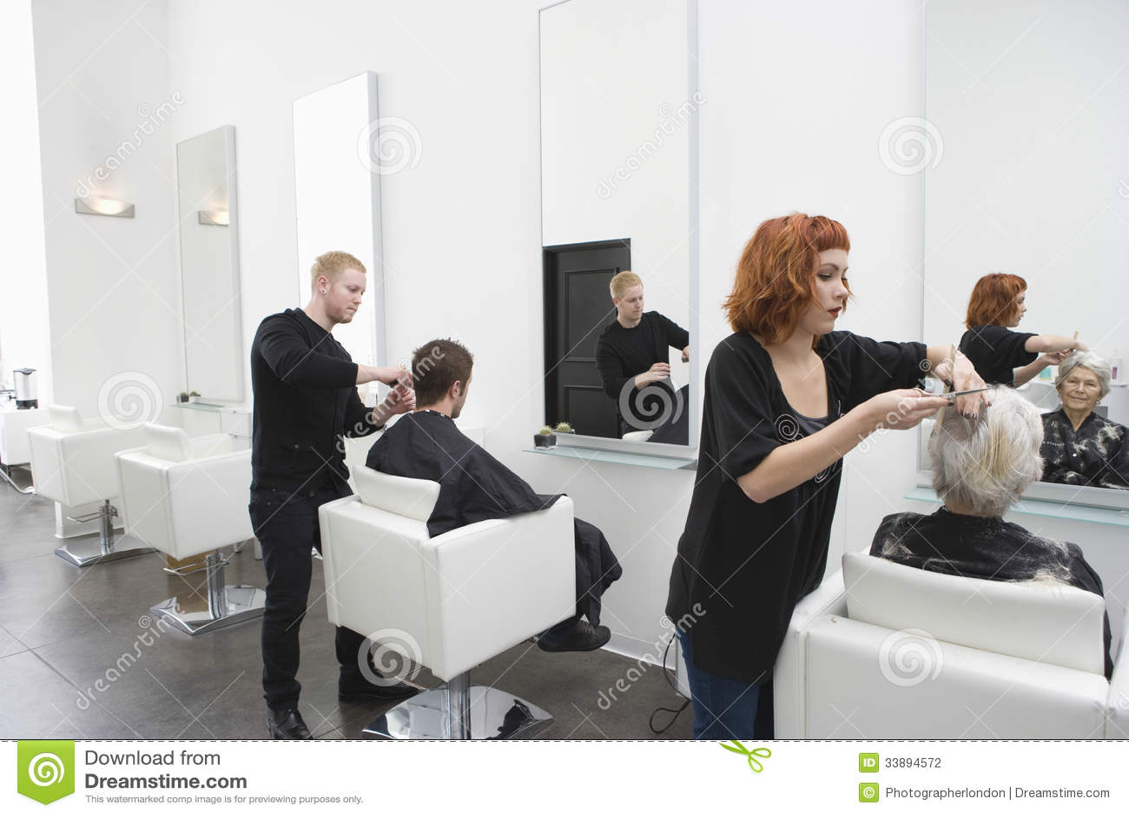 Парикмахеры давая стрижку к клиентам