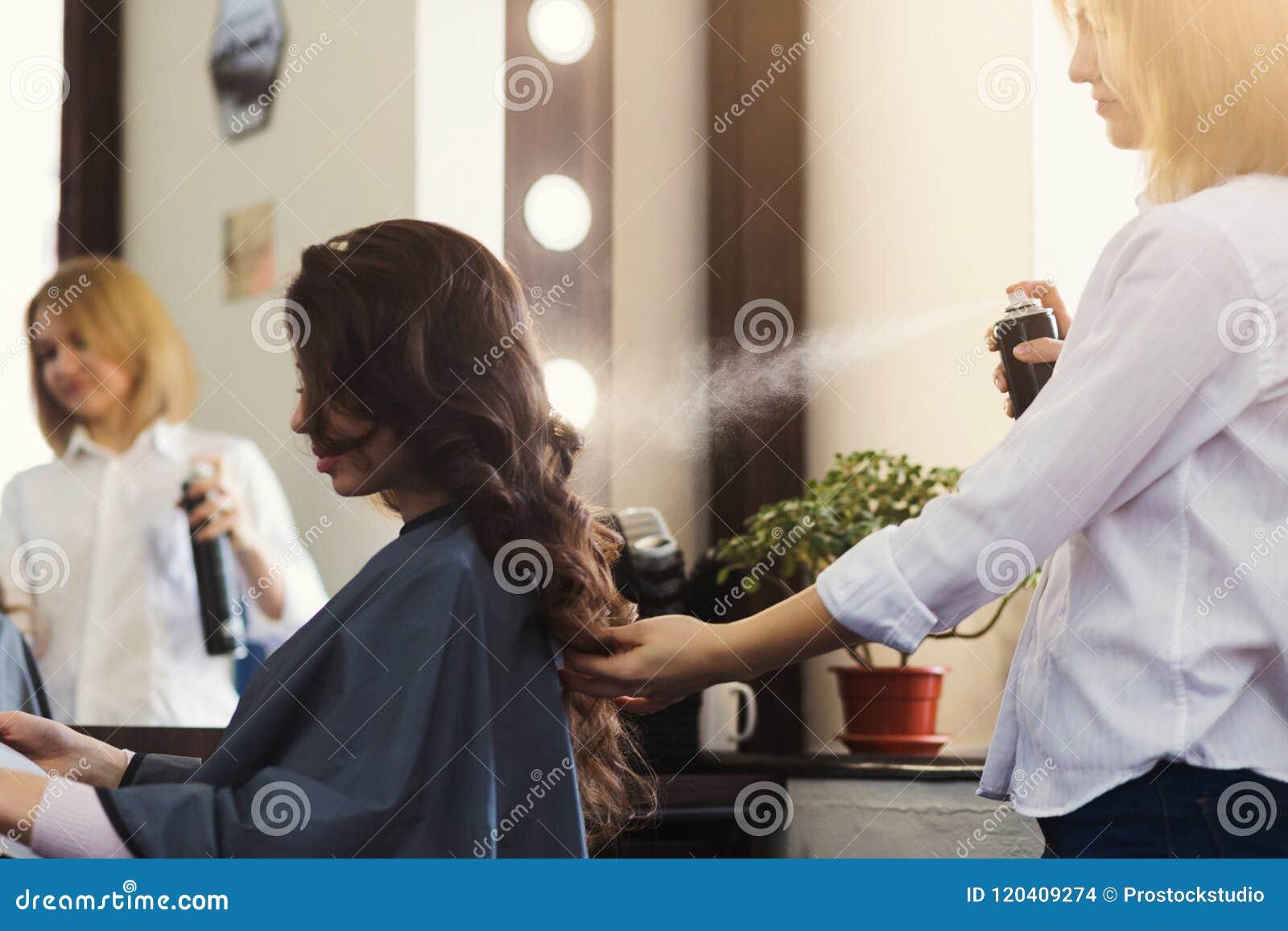 Парикмахер делая курчавый стиль причёсок на салоне красоты