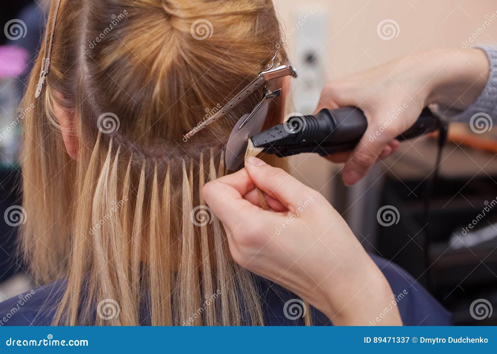 Парикмахер делает расширения волос к маленькой девочке, блондинке в салоне красоты
