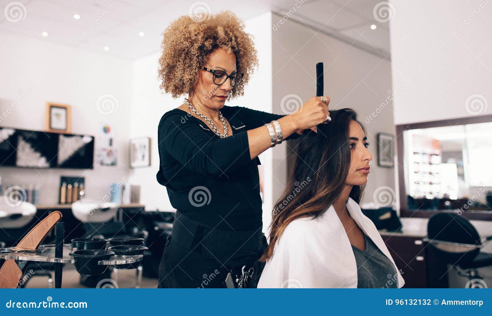 Парикмахер женщины на работе в салоне
