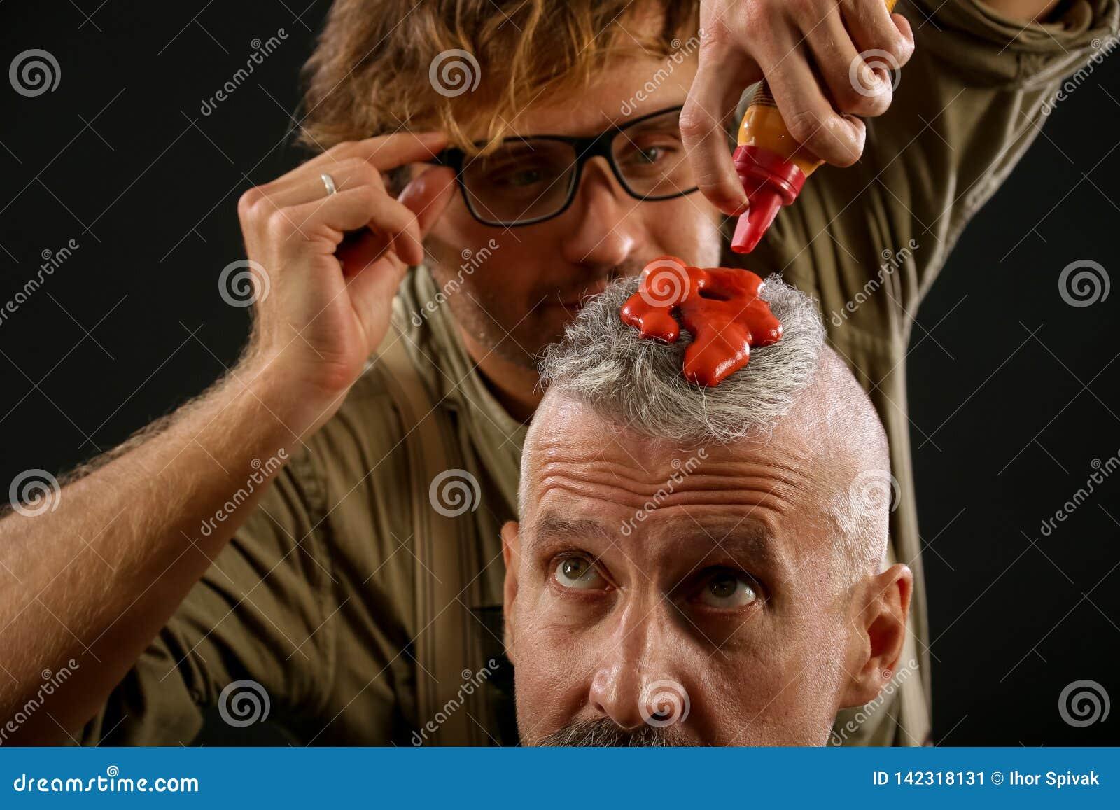 Парикмахер красит с рыжеватой краской пожилого седого гражданина