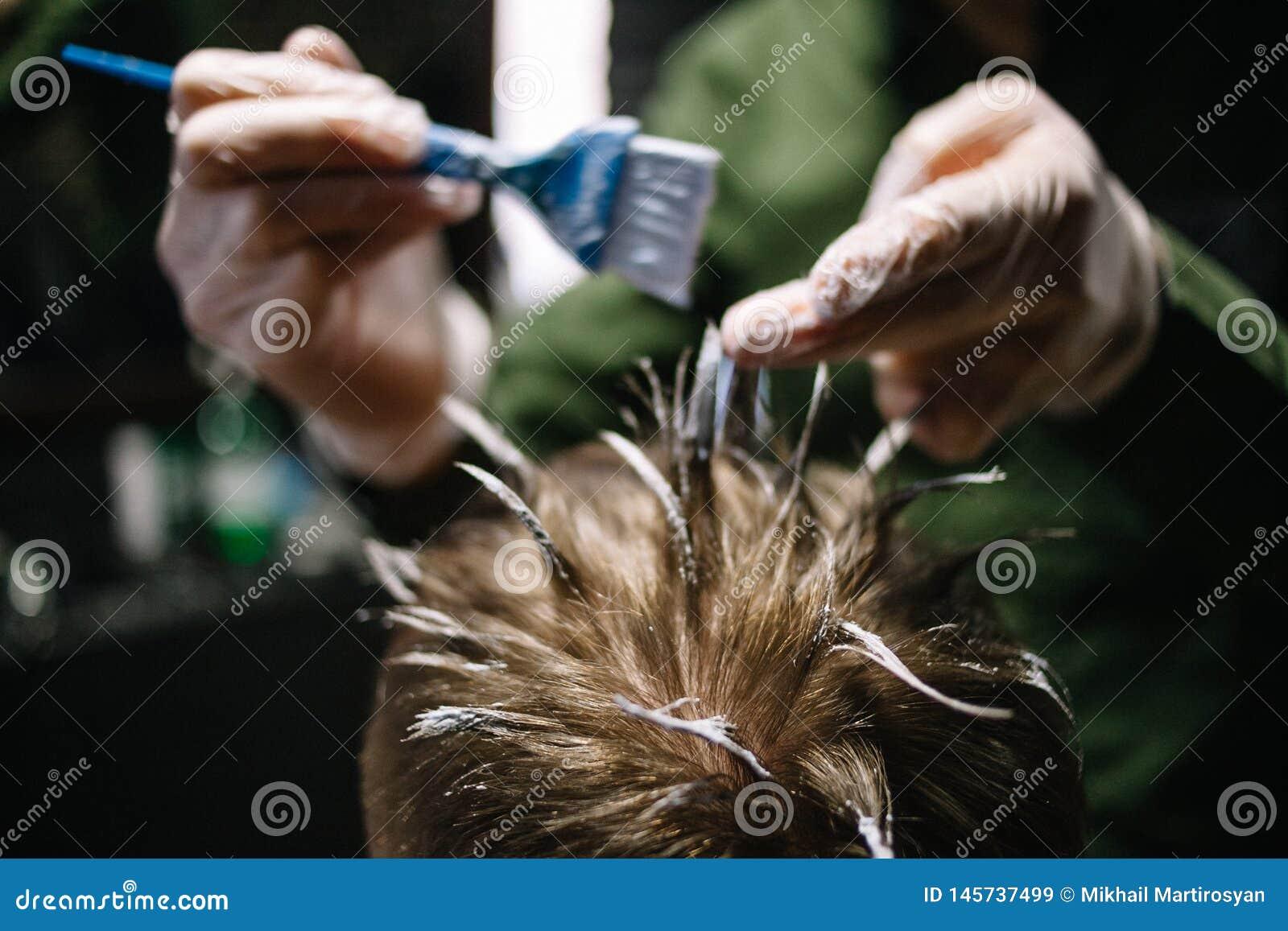 Парикмахер с щеткой для приложения краски волос Красить в парикмахерской