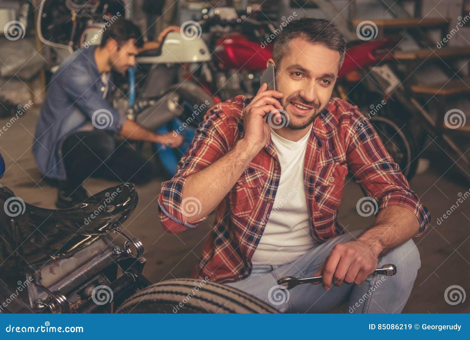 Парни на ремонтной мастерской мотоцилк