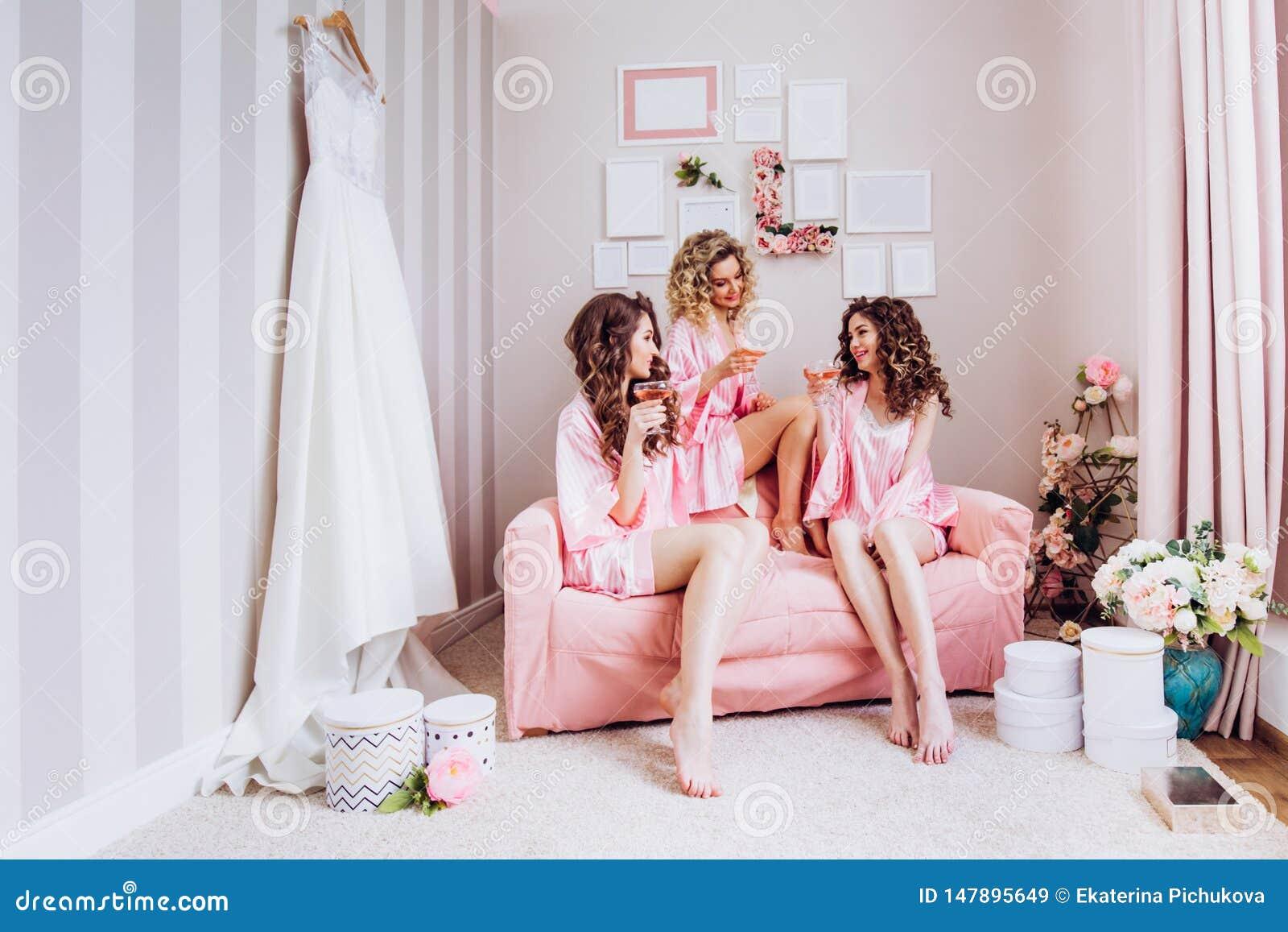 Партия для девушек Девушки выпивают розовое шампанское перед свадебной церемонией в розовых пижамах