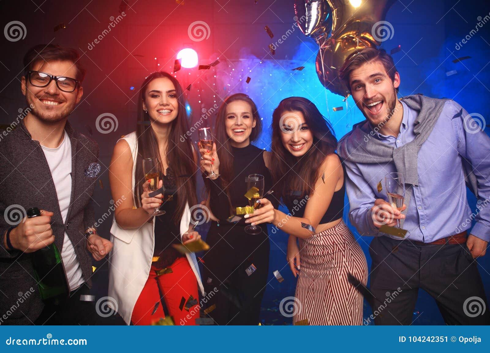 Партия Нового Года, праздники, торжество, ночная жизнь и концепция людей - молодые люди имея танцы потехи на партии