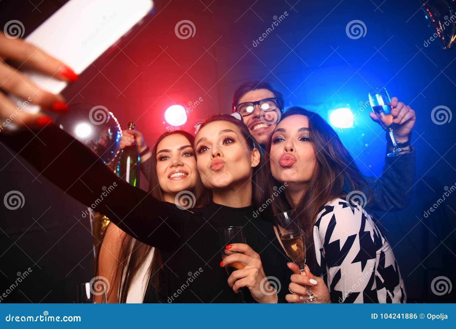 Партия, технология, ночная жизнь и концепция людей - усмехаясь друзья при smartphone принимая selfie в клубе