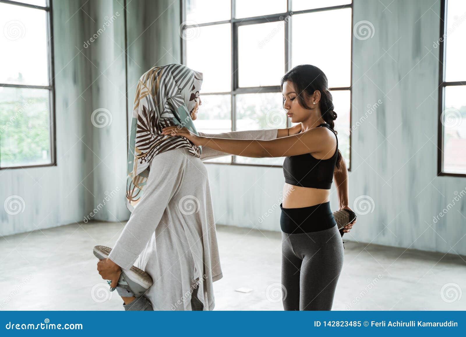 Партнер 2 sporty девушки делая протягивать перед тренировкой ядра