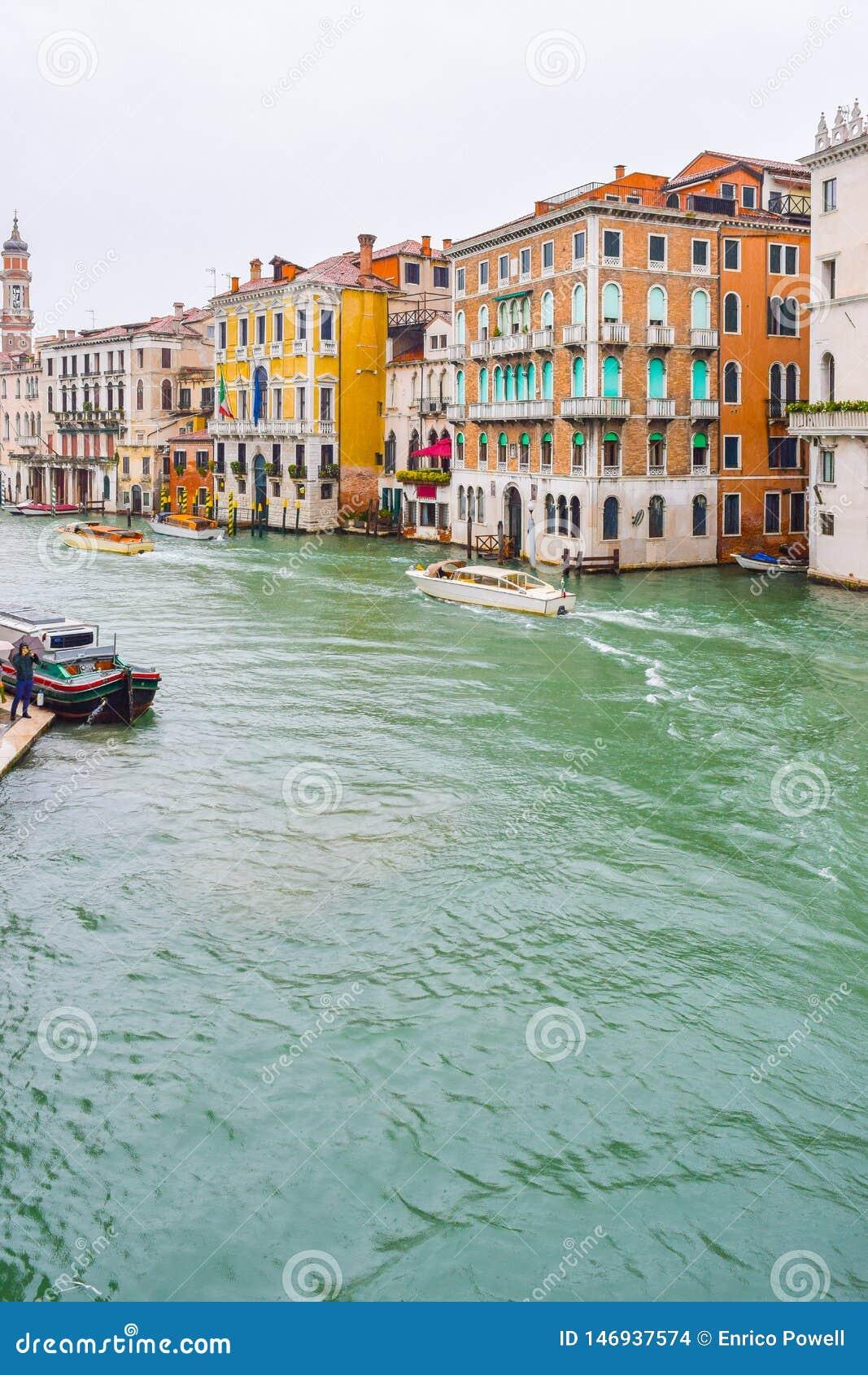 Парусники людей и такси воды около готических венецианских зданий на дождливый день в ноябре на водном пути большого канала, Вене