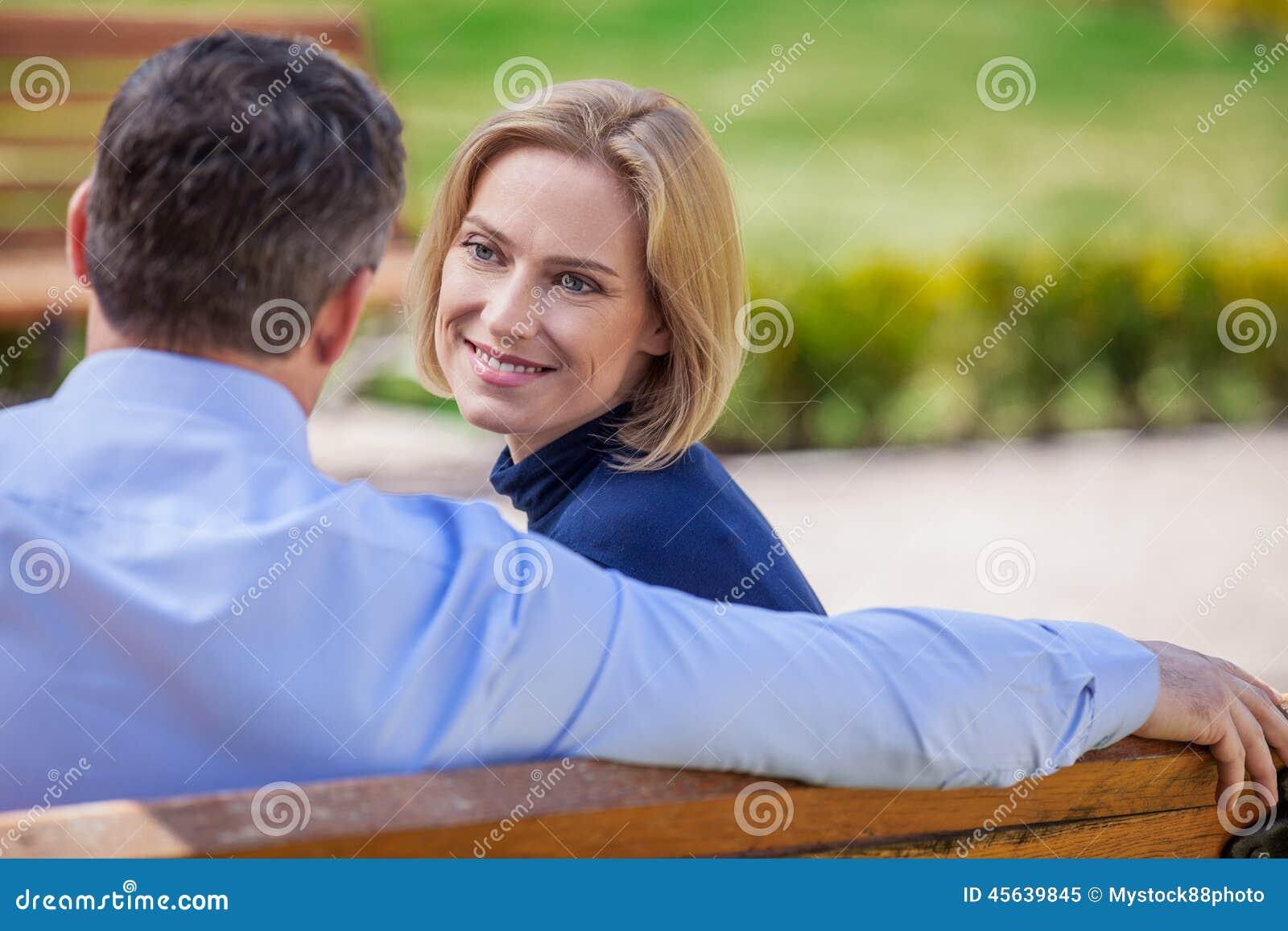 Пары взрослого усмехаясь смотря на одине другого сидя на стенде