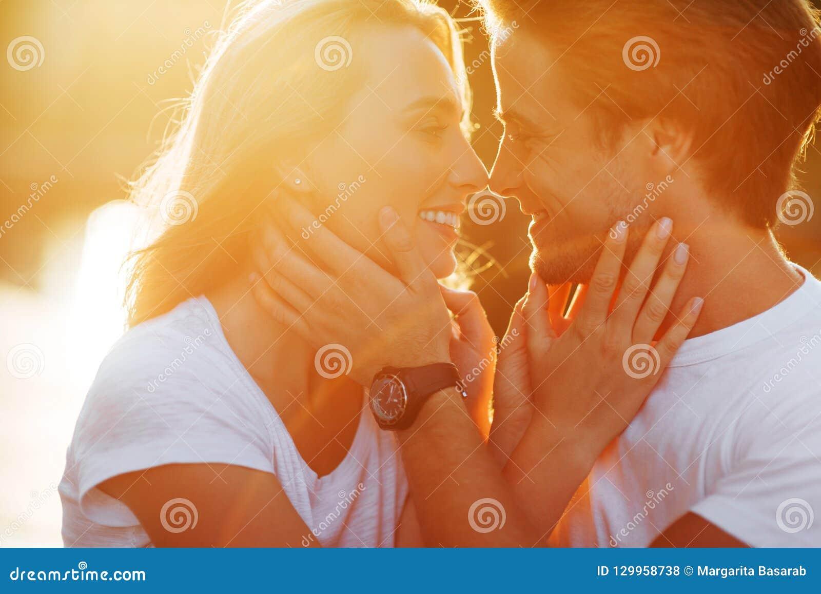 Пары в влюбленности наслаждаясь моментами во время захода солнца