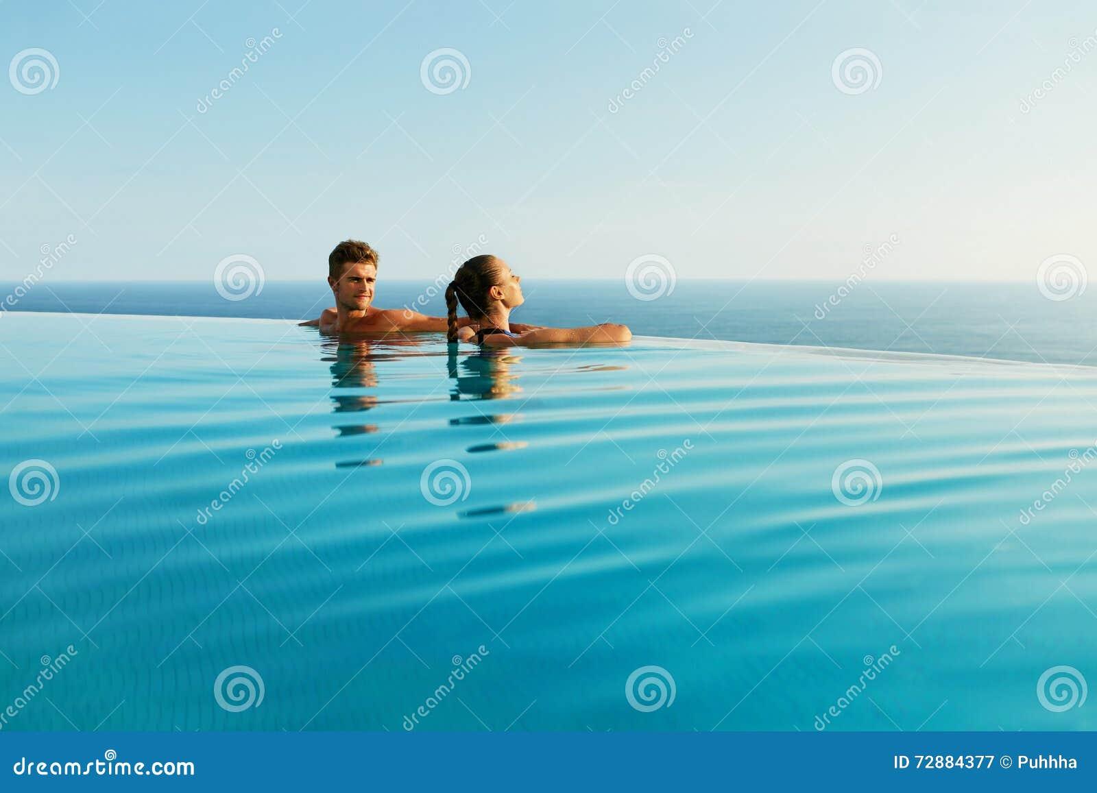 Пары в влюбленности в бассейне роскошного курорта на романтичных летних каникулах